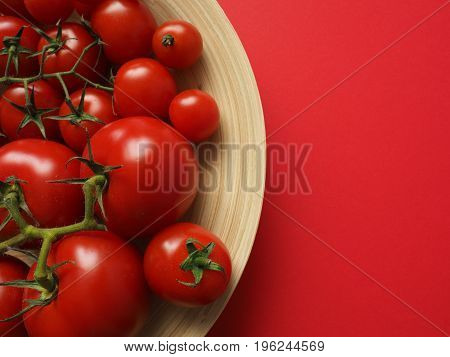 Assortment of delicious tomatoes in a bamboo bowl on a red background