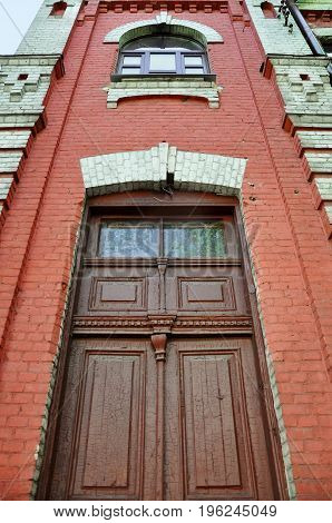 Look up at old red brick building with brown wooden door and arched window. Grodno, Belarus.