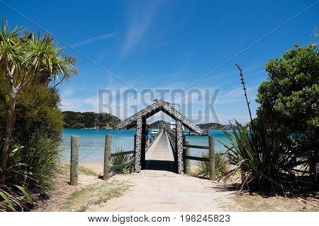 Urupukapuka Island Bay of Islands New Zealand NZ - February 1 2017: Tourist ferry pier has an archway decorated with Maori art.