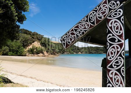 Urupukapuka Island Bay of Islands New Zealand NZ - February 1 2017: Maori art by a white sandy beach.
