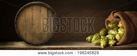 blurred background of brown barrels and hop in basket.