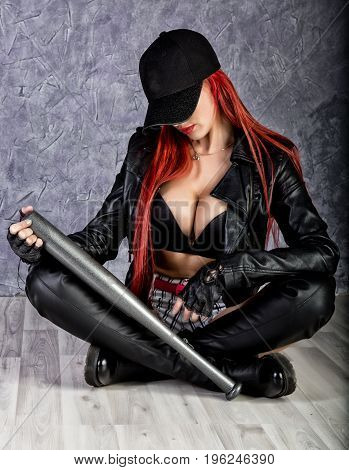 Stylish hipster woman with big tits in baseball cap and black jacket sitting on a floor, holding baseball bat