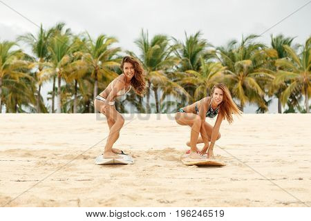 Two Beautiful Sporty Surfer Girl At The Beach.
