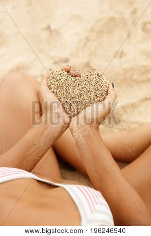 Hands hold sand in shape of hart above tropical beach. Beautiful fit sporty surfing girl in sexy bikini sit at sunrise or sunset on a beach. Vacation concept. Summer holidays. Love is everywhere.