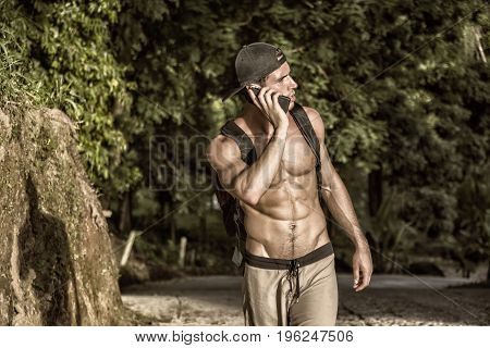 Young muscular topless man with backpack and phone looking away on background of tropical forest.