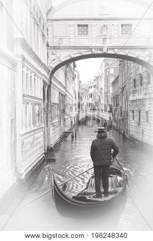Gondolier on the canal under the Bridge of Sighs in Venice