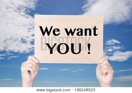hand holding we want you! sign on blue sky background