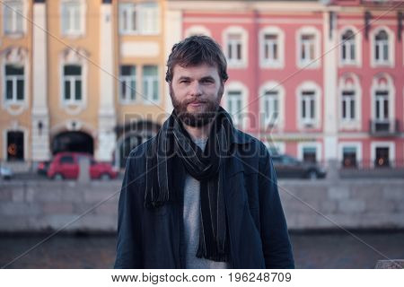 Portrait of young man walking on the Fontanka river embankment. Historical centre of St. Petersburg.