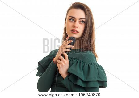 charming woman in green color dress with microphone in hands isolated on white background