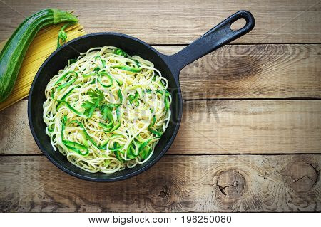 Pasta with zucchini on dark wooden background in a cast-iron frying pan . Spaghetti from organic wholegrain flour.