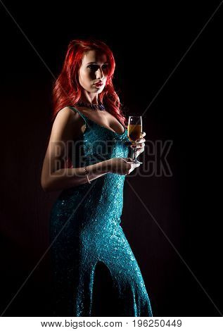 Young redhead sexy woman in blue elegant dress holding wineglass with champagne and poses in a dark