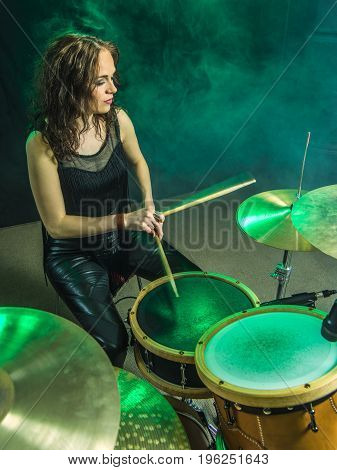 Photo of a beautiful woman playing her drum set on stage.