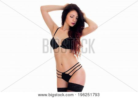 beautiful slim brunette in black lingerie with closed eyes isolated on white background