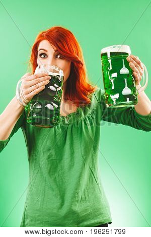 Photo of a beautiful redhead woman holding and drinking two huge green beers.