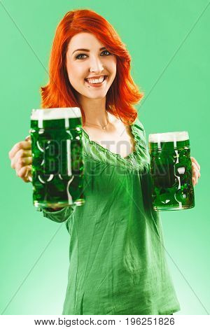 Photo of a beautiful redhead woman holding and drinking two huge green beers on St Patricks Day.