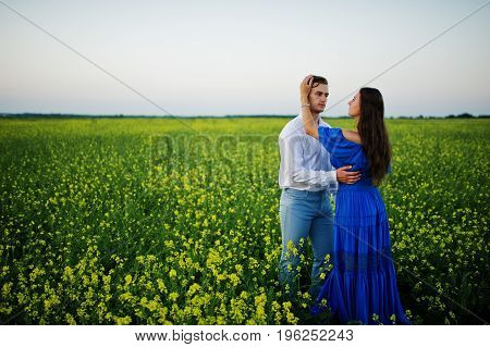 Attractive Young Couple Walking On The Field Full Of Yellow Flowers.