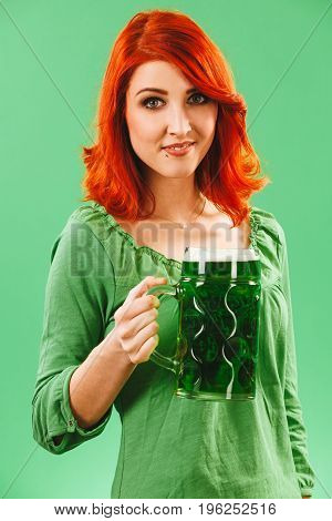 Photo of a beautiful redhead woman holding and drinking a huge green beer.