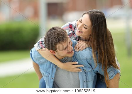 Front view of a happy couple of teens joking together piggyback outdoors in a park with a green background