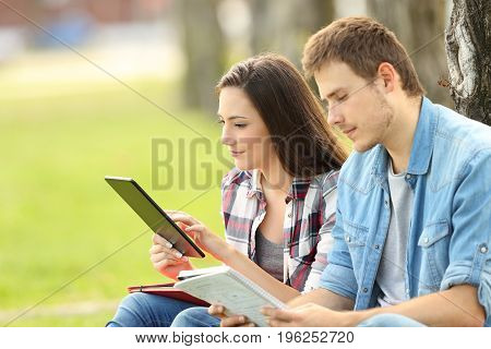 Two students studying on line and reading notes sitting on the grass in a park