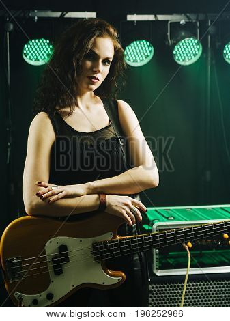 Photo of a beautiful young bass player standing on stage with her guitar.