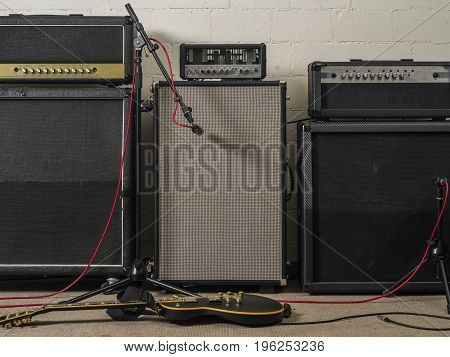 Photo of three guitar amplifiers in a recording studio setting with microphone and electric guitar.