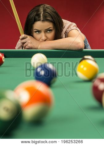 Photo of a beautiful brunette at the edge of a billiards table holding a pool cue and wondering about her next shot.
