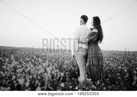 Attractive Young Couple Walking On The Field Full Of Yellow Flowers. Black And White Photo.