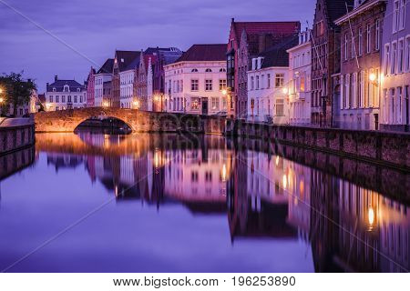 Jan van Eyckplein old town of Bruges Belgium during sunset with reflection on water.