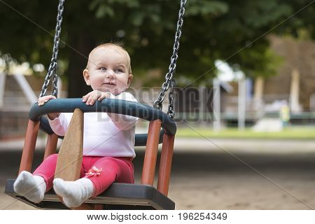 small active child happily swings on a swing in a summer park