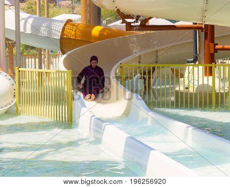 TURKEY, BELEK - 14 JULY 2017: The Land of Legends Theme Park. Arabian woman sliding down on water-slide in waterpark.