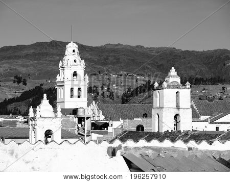 White colonial bell towers and orange rooftops in Sucre, Bolivia, South America. Black and white image.