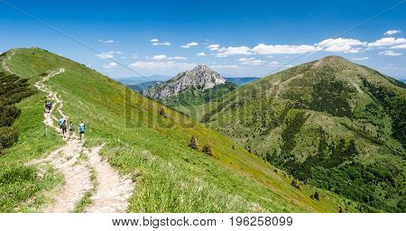 Steny Velky Rozsutec and Stoh hills with hiking trail with hikers in Mala Fatra mountains in Slovakia during nice day with blue sky and only few clouds