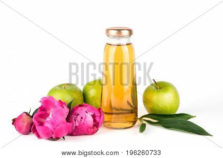 Apple golden juice in bottle. Fruit soft drink in a glass bottles isolated on white background. Pink flowers peonies