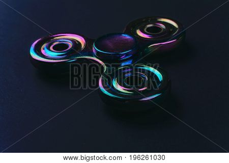 Hand fidget spinner toy on black background. Stress and anxiety relief.
