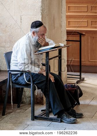Jerusalem Israel July 14 2017 : Religious Jewish man reads prayers in the Tomb of King David in the old city of Jerusalem Israel