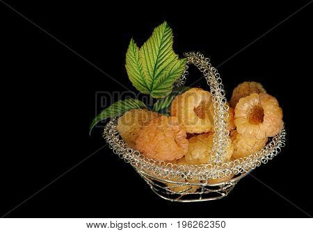 Yellow ripe raspberries in a small openwork metal basket on a black background.