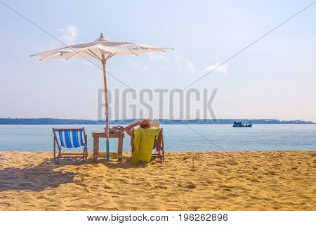 A lady chilling out on beach chair at a beautiful beach under white beach umbrella