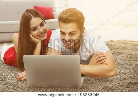 Young couple using laptop for browsing internet store at home. Online shopping concept