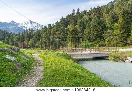 A pedestrian bridge crossing a small river with fresh glacier water in the National Park Tuéda. The french alps are in the background.