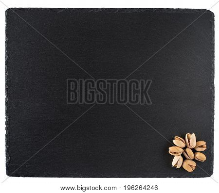 Pistachio nuts on a black slate board. Isolated on white background. Top view.