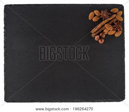 Almonds cinnamon and star anise on a black slate board. Isolated on white background. Top view.