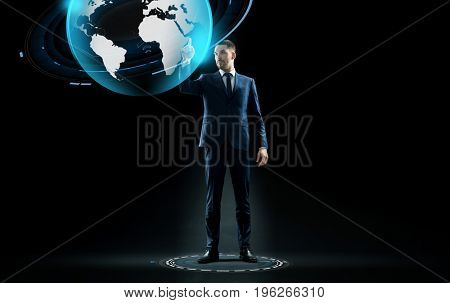 business, people and technology concept - businessman in suit touching earth globe hologram over black background