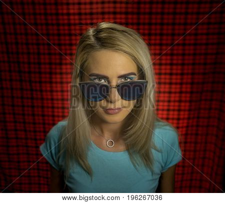 Portrait of a trendy hipster girl in glasses standing on a red checkered background. The concept of urban fashion. Turquoise shades. Portrait