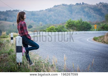 Tourist Hitchhiking Woman Standing On The Road In The Mountains.