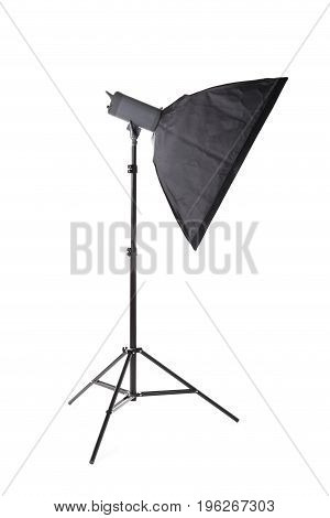 A long and new saturated black softbox isolated over the white background. Photographic lighting equipment. Stripbox on a metal tripod. Photography, shooting, technique concept.