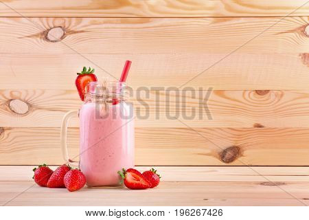 Homemade strawberry smoothie in a mason jar on a light wooden background. Vegetarian milkshake in a transparent jar with tasty juicy strawberries. Healthy beverages for a breakfast.