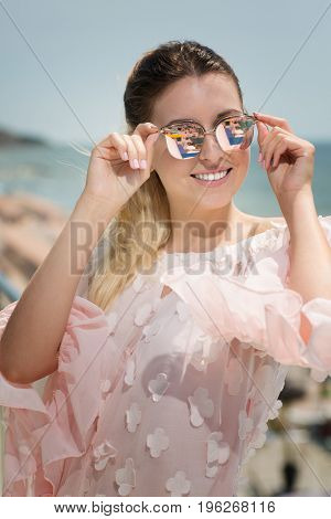 A portrait of a smiling young woman on a sunny resort background. A beautiful lady in big bright sunglasses wearing a light rose dress. A stunning lady having fun on a summer vacation.