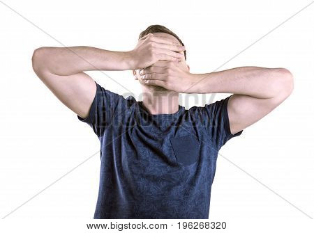 A stressed student covering his face isolated over the white background. A depressed guy with a stubble and light brown hair. A strong young man in a dark blue cotton t-shirt.