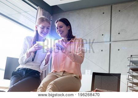Smiling young businesswomen using mobile phone in office