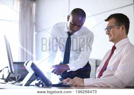 Businessman showing something to male colleague on laptop at office desk